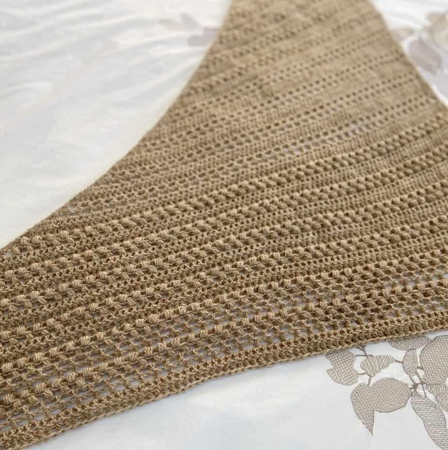 a textured, beige triangular crochet shawl laid flat on a white bed sheet