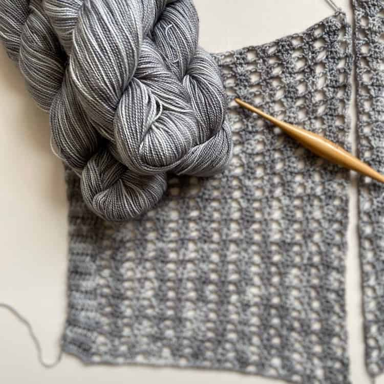 grey fingering weight yarn in hanks laid on crochet lace panel with wooden crochet hook