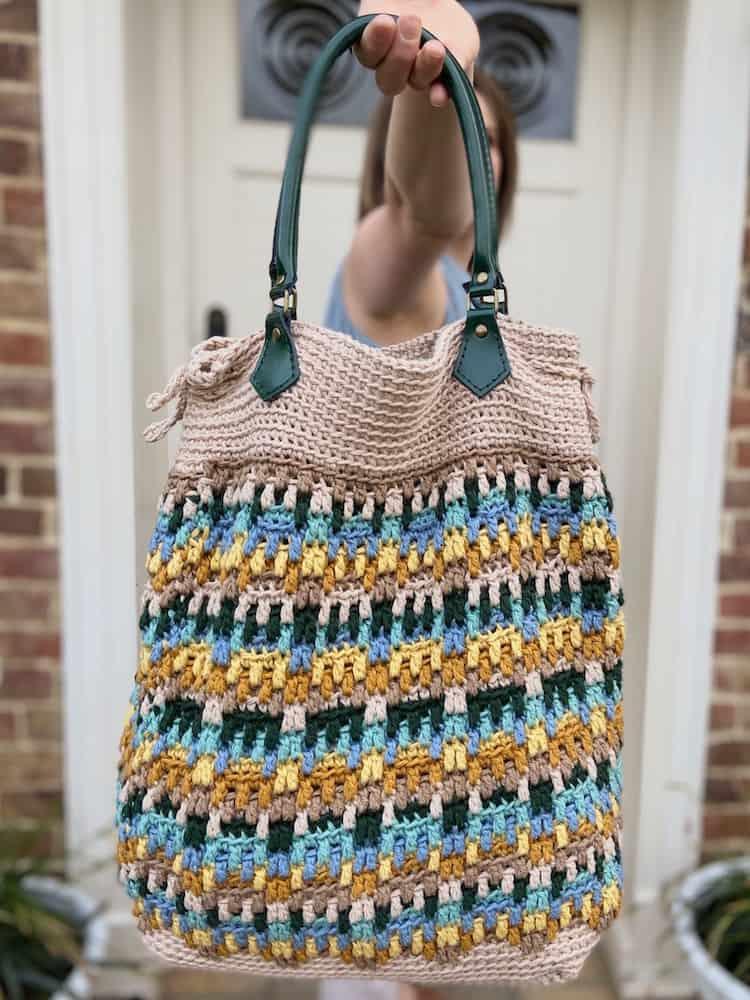 woman holding up mosaic crochet tote bag