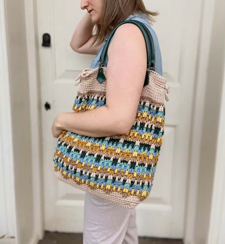 woman with crochet tote bag over shoulder and arm clasped around it