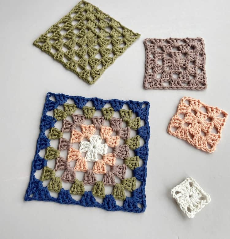 five different size and colour crochet granny squares