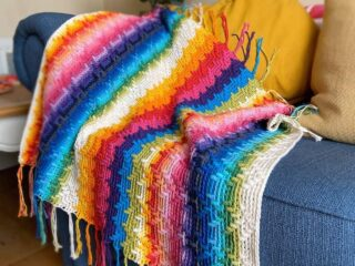 rainbow overlay mosaic crochet blanket on a blue sofa