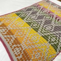 Wanderers Mosaic Crochet Blanket pattern spread out on bed