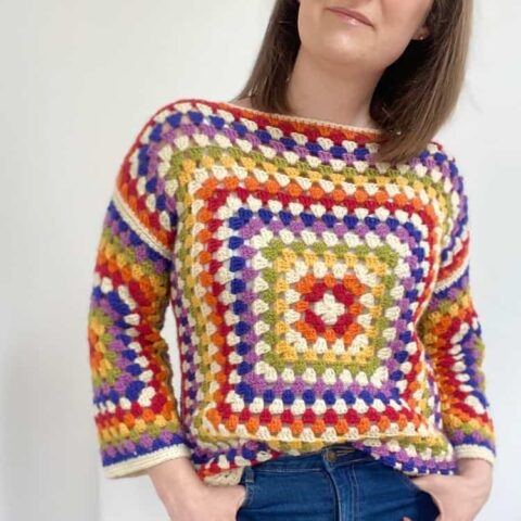 woman wearing rainbow granny square sweater and jeans