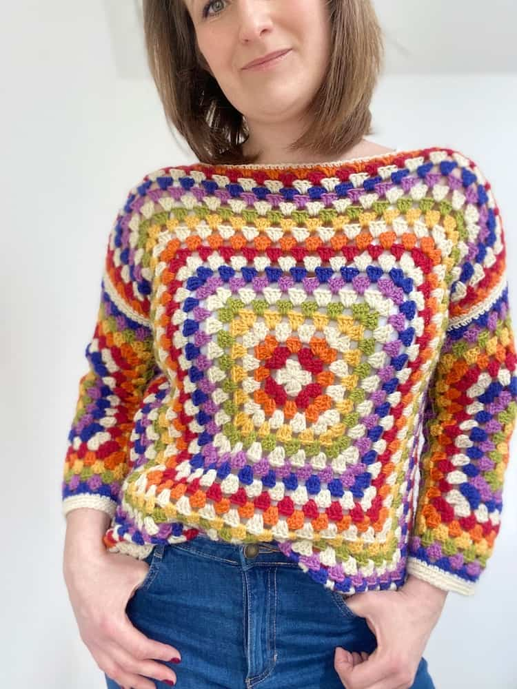 woman wearing rainbow granny square sweater with hands in jeans pockets