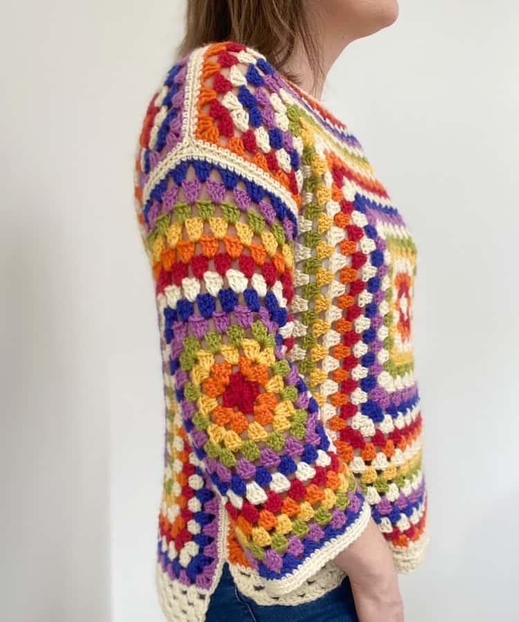 person wearing rainbow crochet sweater facing sideways