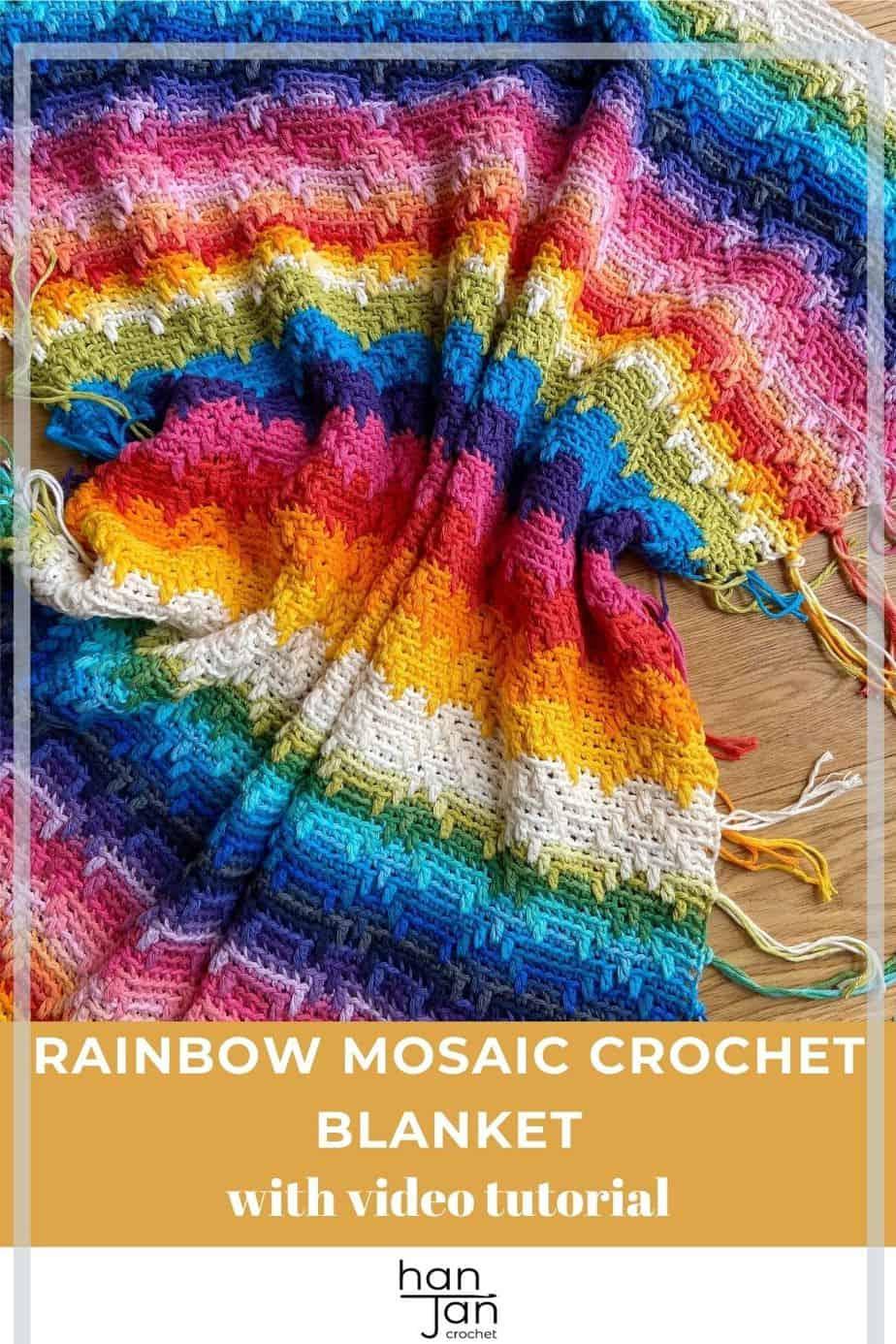 rainbow crochet blanket using overlay mosaic crochet technique with tassels laid on wooden floor