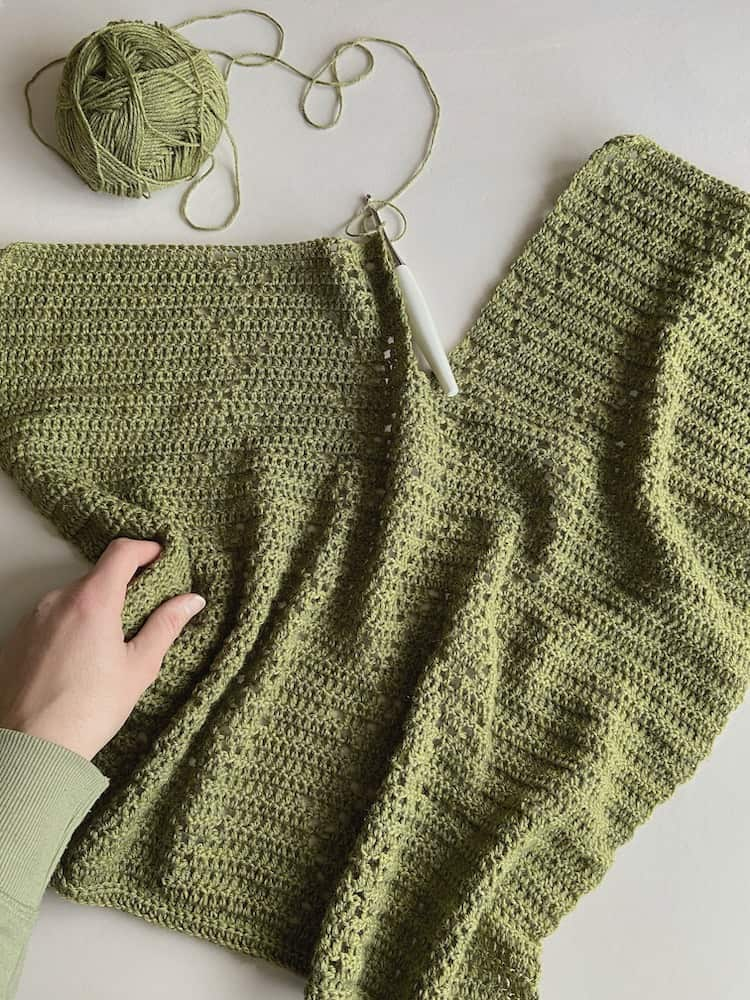 progress image of crochet t-shirt in green with hand holding the crochet and white crochet hook in place and ball of yarn