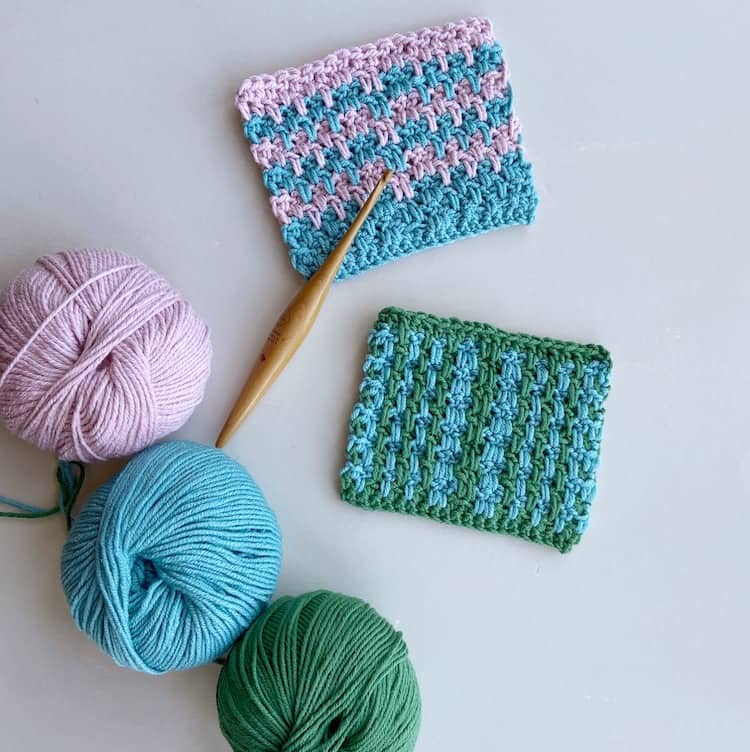 two double crochet moss stitch swatches with wooden Furls crochet hook and three balls of yarn