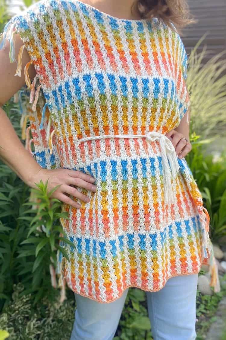 woman in garden wearing colourful summer crochet poncho