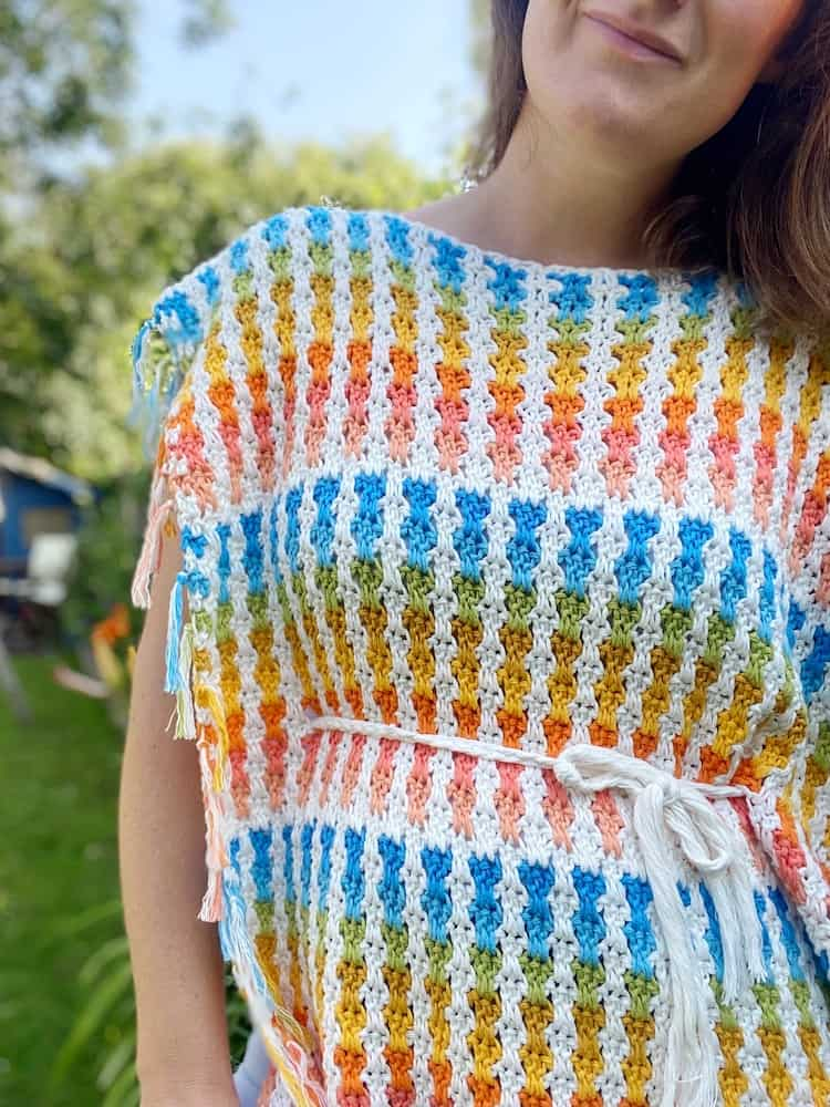 woman wearing colourful crochet poncho with white braided belt around waist