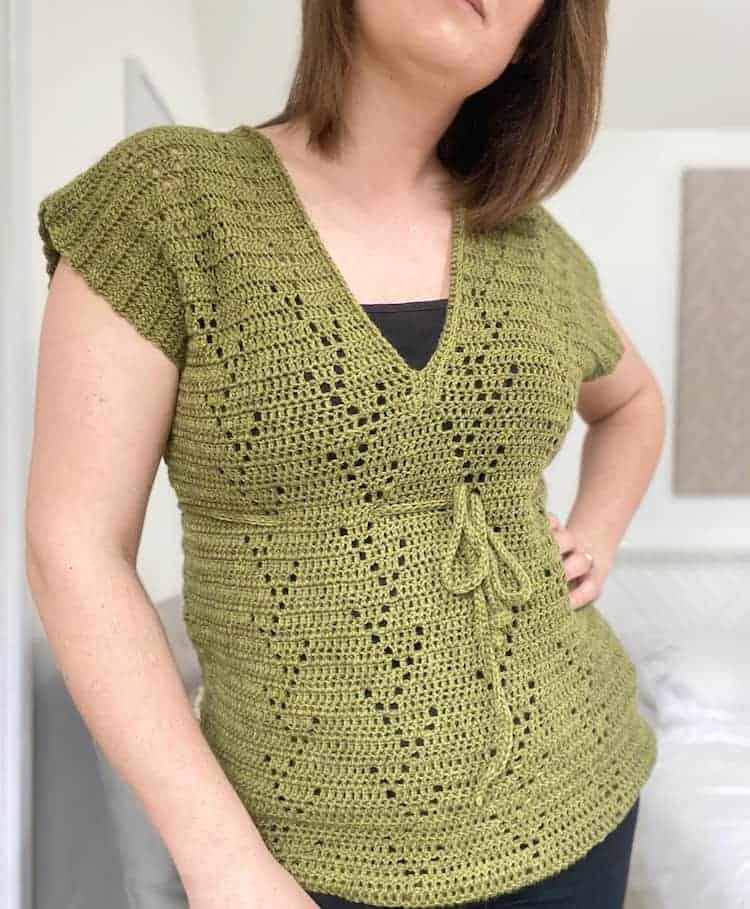 woman wearing green filet crochet t-shirt with hand on hip