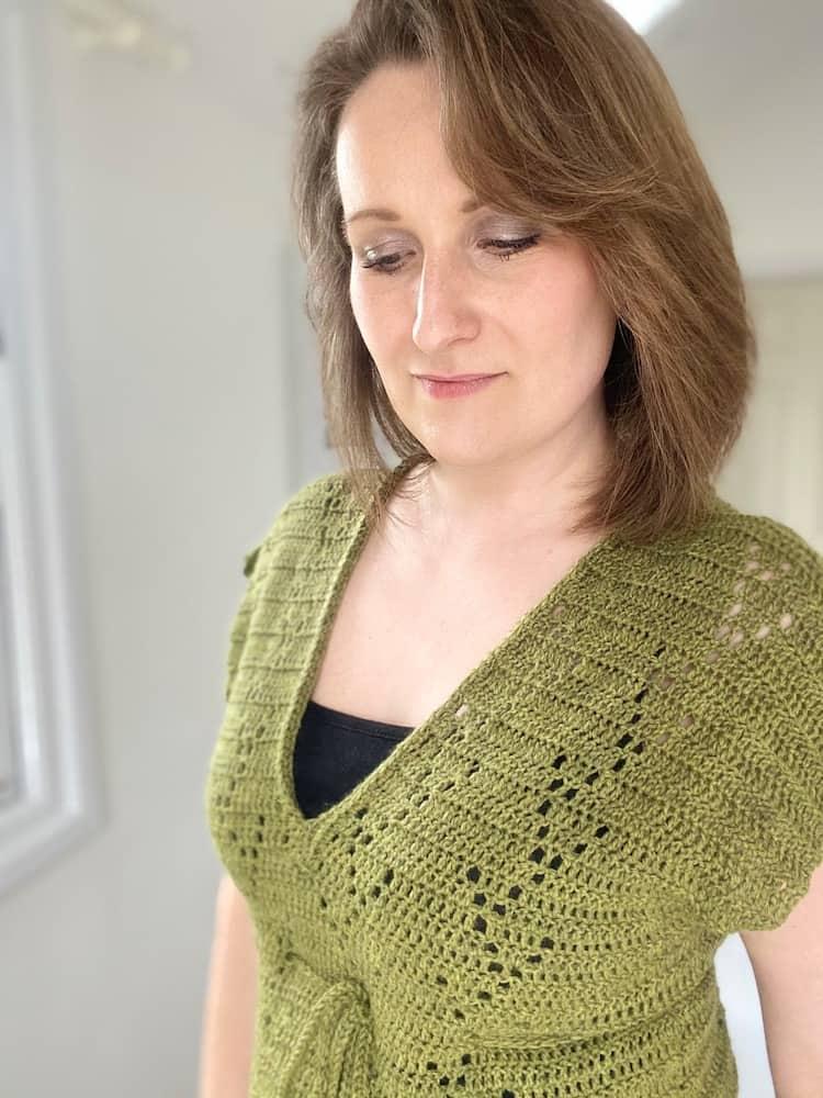 woman looking down wearing V neck crochet t-shirt with filet crochet detail