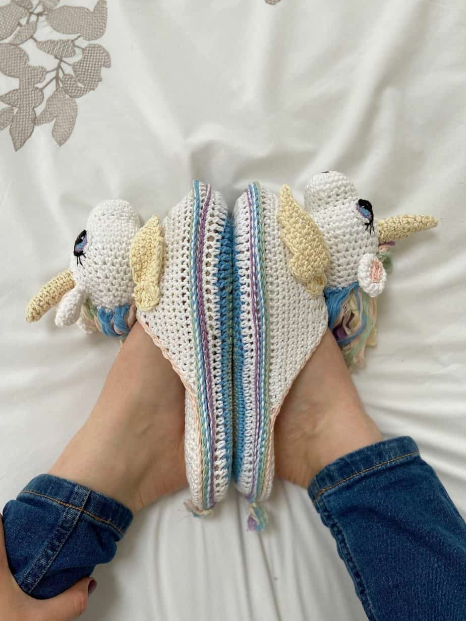 overhead image of person wearing unicorn crochet slippers pattern with soles together in lotus position