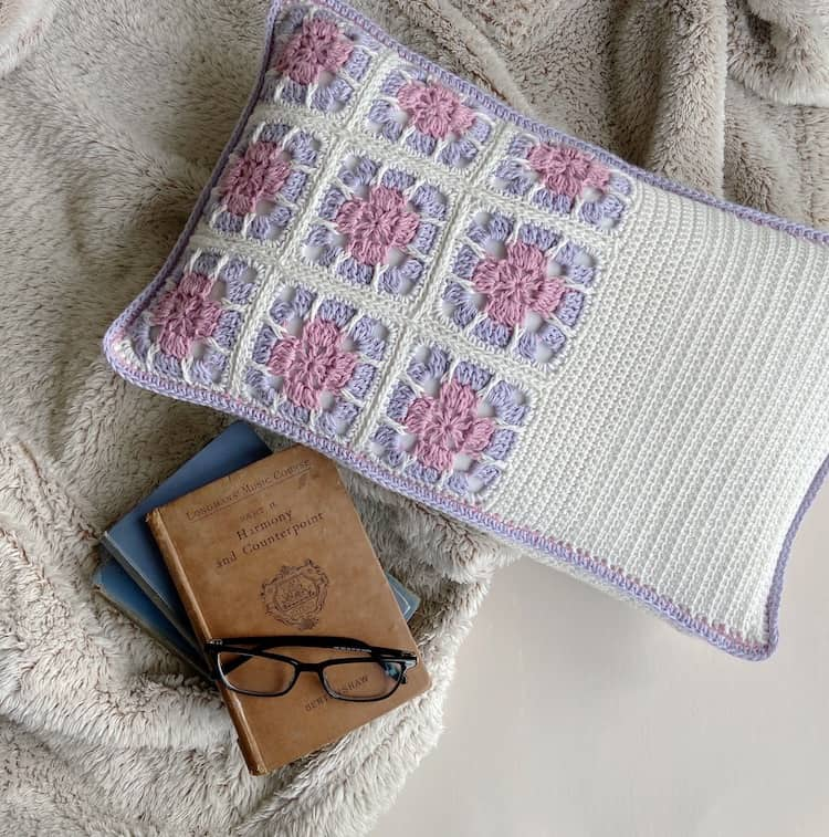 floral granny square cushion in pink, lilac and white next to a pile of books and glasses
