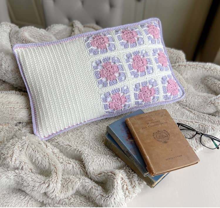 9 crochet floral granny square motifs on cushion cover in white, pink and lilac