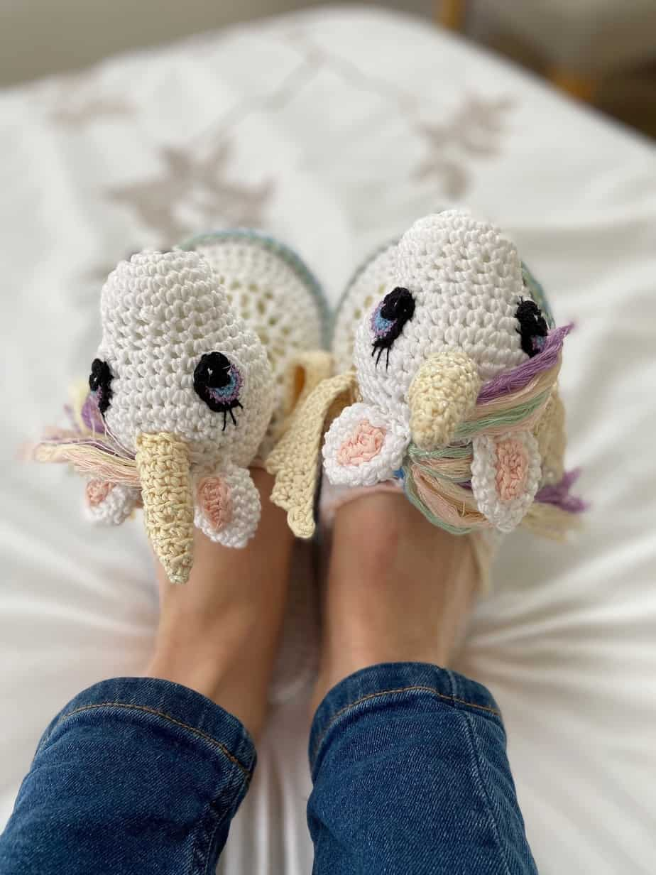 person wearing unicorn crochet slippers with horns, rainbow mane and wings