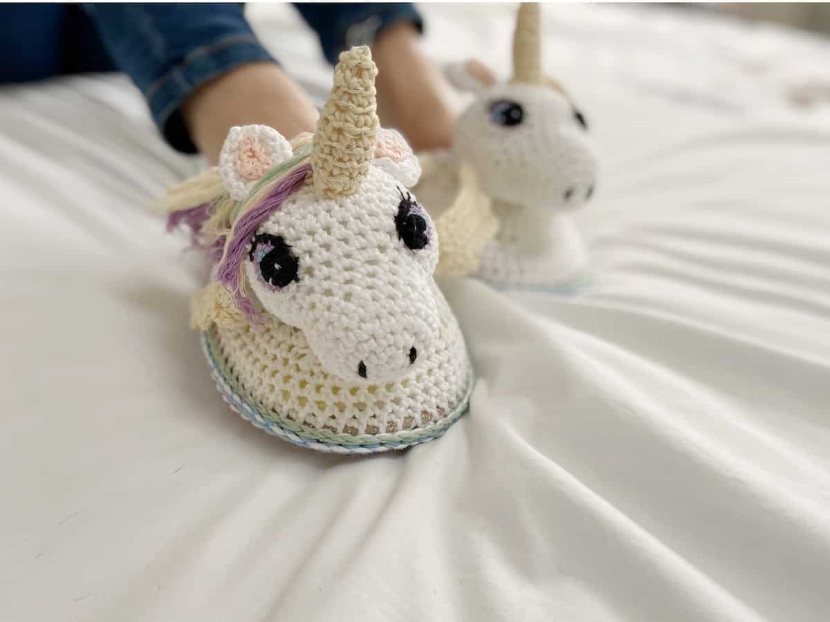 close up of amigurumi unicorn crochet slippers on a someone wearing blue jeans
