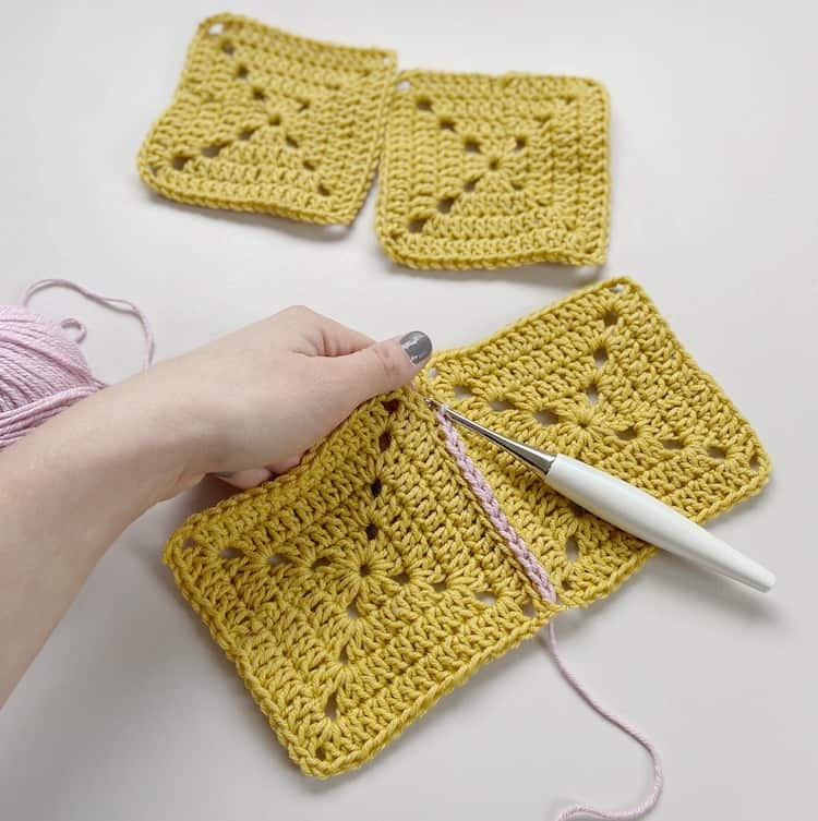 Joining crochet squares together in yellow and pink yarn
