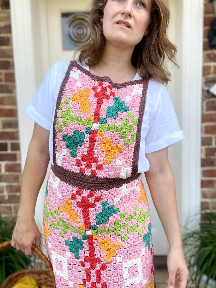 woman moving forwards wearing retro crochet apron with bright pattern