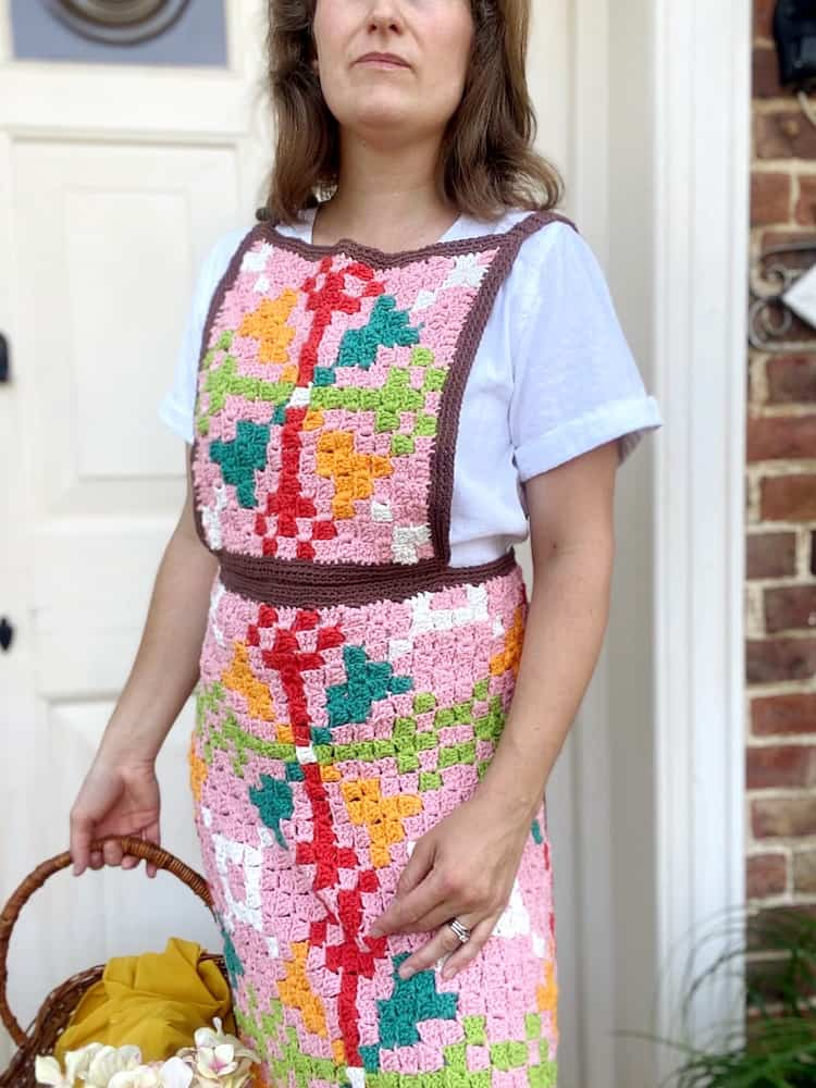 woman wearing c2c crochet apron in vintage colours with a retro geometric design