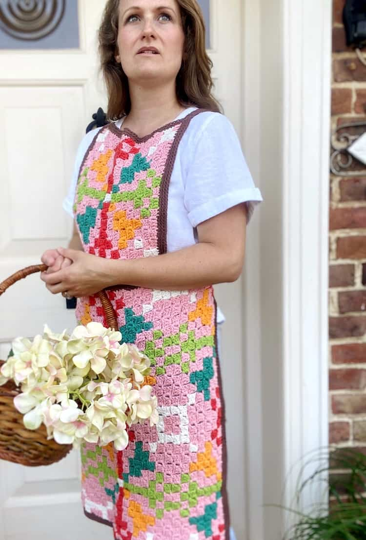woman looking up wearing white shirt and geometric crochet apron in c2c method