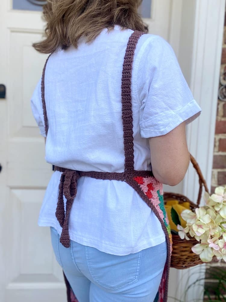 image of back of crochet apron being worn by woman holding basket