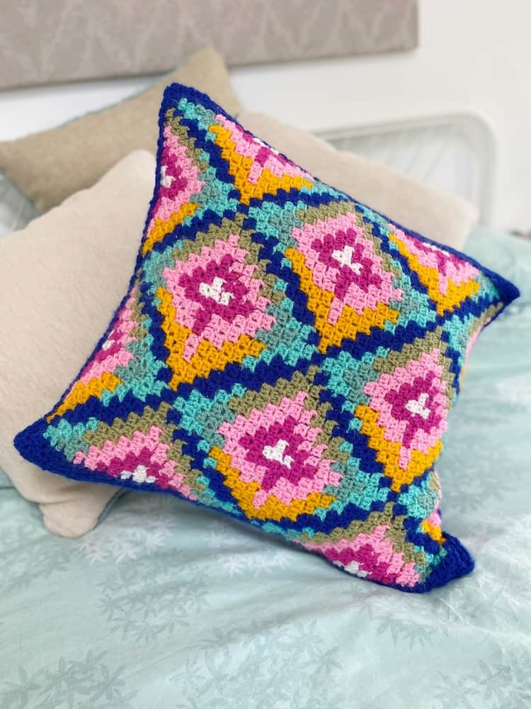 Bargello inspired colourful c2c crochet pillow on bed