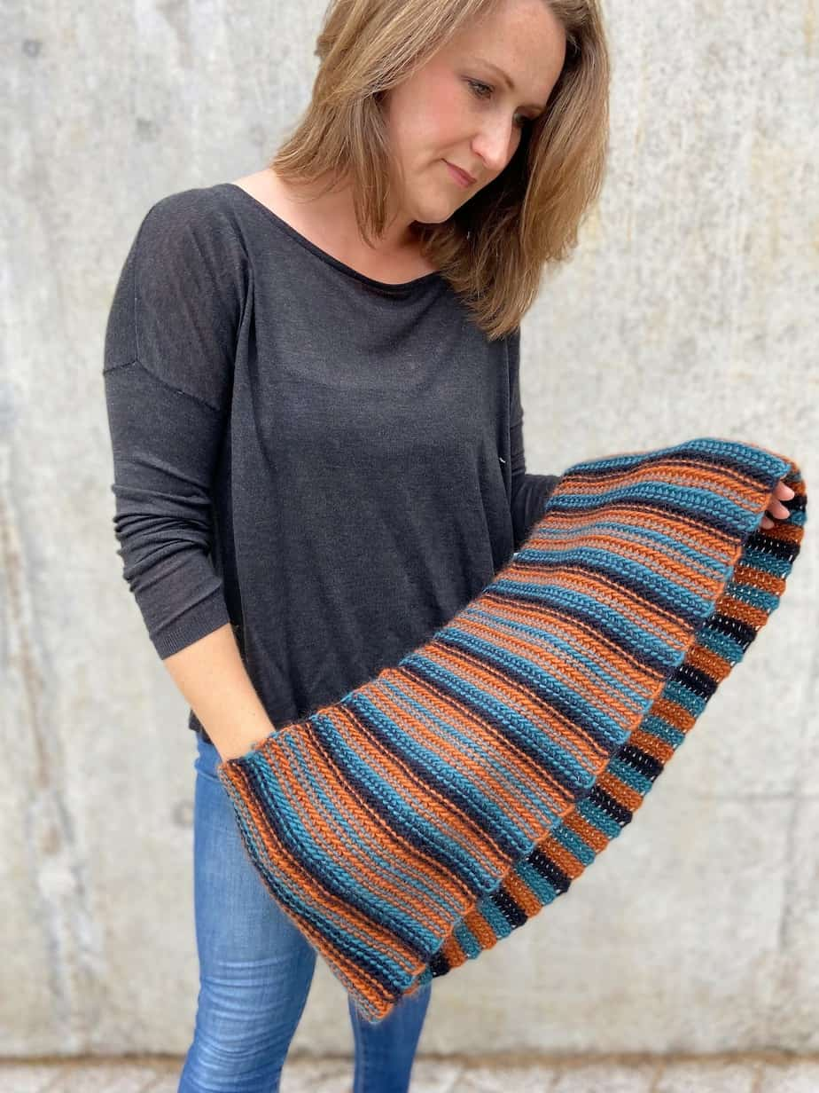 person in jeans and jumper holding chunky crochet cowl across hands