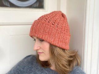 slouchy crochet hat pattern worn by woman against a cream door