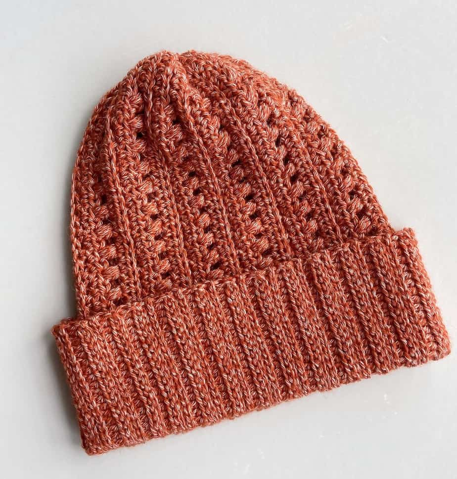 flatlay image of slouchy crochet hat pattern in a rusty orange colour and knit look wide brim