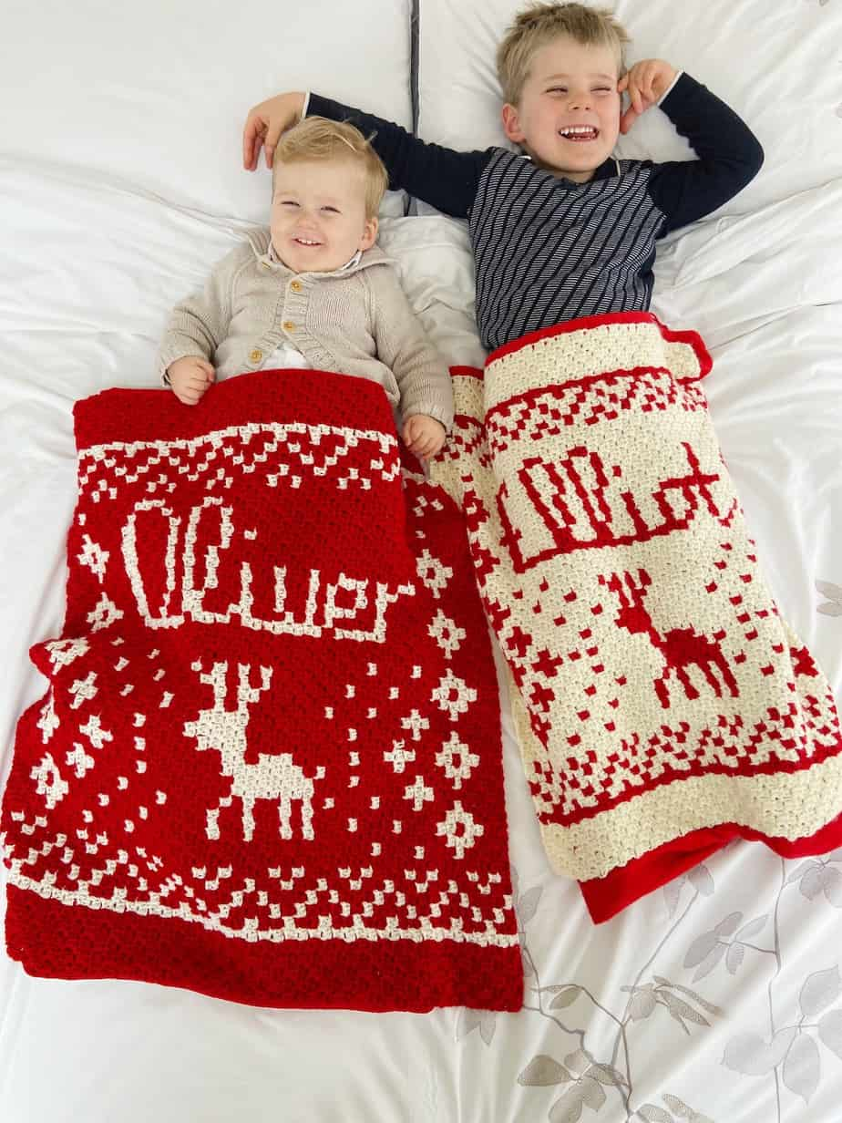 two children under c2c Christmas crochet blankets with their names on