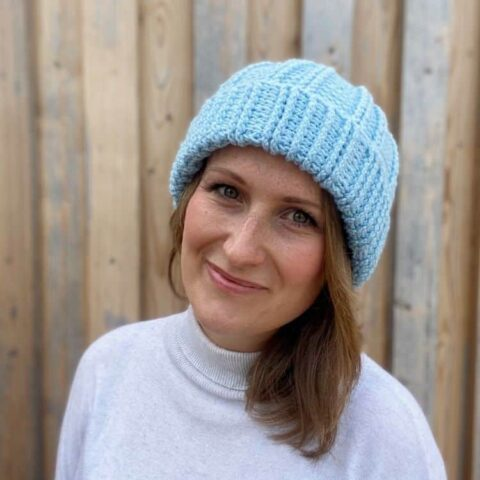 blue textured crochet bobble hat worn by a woman
